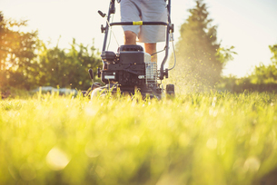 Midsection of man mowing grassy field against sky in yard during sunsetの写真素材 [FYI03749050]