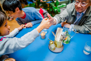 Grandson and grandfather playing thumb wrestling at restaurantの写真素材 [FYI03749221]