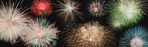 Panoramic view of colorful firework display exploding against sky at nightの写真素材 [FYI03749289]