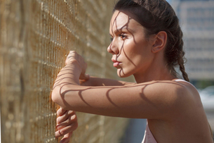 Side view of thoughtful woman looking through metallic fence while standing in city during sunny dayの写真素材 [FYI03749378]