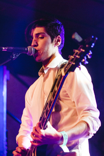 Confident male singer singing and playing guitar in nightclubの写真素材 [FYI03749386]