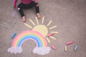 Low section of girl drawing colorful chalks on streetの写真素材 [FYI03749422]