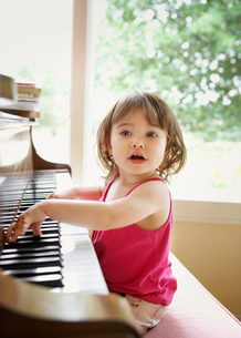 Curious baby girl looking away while playing with pianoの写真素材 [FYI03749606]