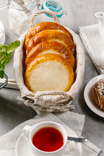 High angle view of buns with cottage cheese in wicker basket served with tea on tableの写真素材 [FYI03749635]