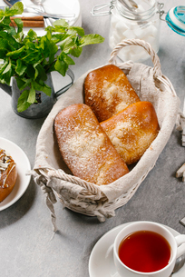 High angle view of buns in wicker basket with tea served on tableの写真素材 [FYI03749638]
