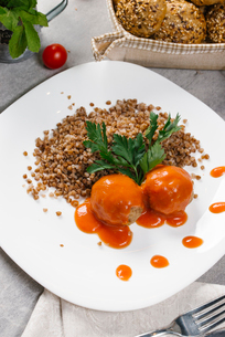 High angle view of boiled buckwheat served with meatballs and tomato sauce in plate on tableの写真素材 [FYI03749641]