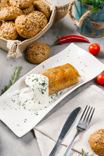 High angle view of stuffed crepe served with sour cream and dill in plate by meatballs on tableの写真素材 [FYI03749650]