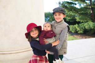 Portrait of smiling siblings standing against column at parkの写真素材 [FYI03749658]