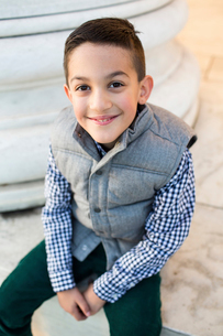 High angle portrait of smiling boy sitting on retaining wallの写真素材 [FYI03749664]