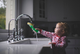 Cute baby girl holding cleaning brush in sink at homeの写真素材 [FYI03749703]