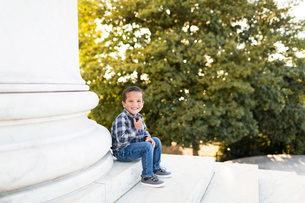 Portrait of smiling boy sitting on steps against trees in parkの写真素材 [FYI03749728]