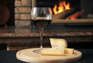 Close-up of wine with cheese slices served on wooden tray against fireplaceの写真素材 [FYI03749735]