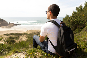 Side view of man with backpack looking at sea while sitting on hill against sky during sunny dayの写真素材 [FYI03749775]