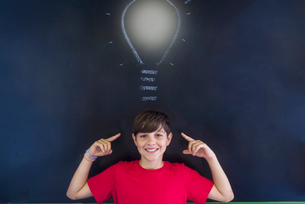 Portrait of smiling schoolboy with light bulb drawing on blackboard standing in classroomの写真素材 [FYI03749844]