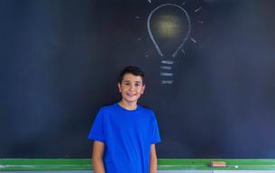 Portrait of schoolboy with light bulb drawing on blackboard standing in classroomの写真素材 [FYI03749850]
