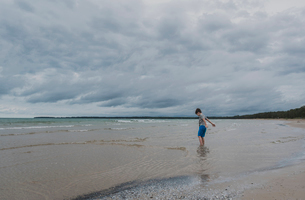 Side view of boy standing in sea against cloudy skyの写真素材 [FYI03749896]