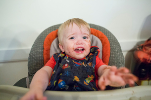 Portrait of messy baby boy crying while sitting on high chair against wall at homeの写真素材 [FYI03749934]