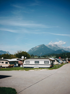Motor homes parked on landscape against blue sky during sunny dayの写真素材 [FYI03750126]