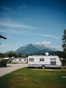 Motor homes parked on field against blue sky during sunny dayの写真素材 [FYI03750128]