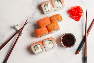 Overhead view of sushi rolls with chopsticks and dip served on tableの写真素材 [FYI03750433]