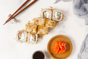 Overhead view of sushi rolls with chopsticks and salmons by dip served on tableの写真素材 [FYI03750436]