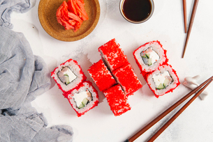 Overhead view of red sushi rolls with chopsticks and salmons by dip served on tableの写真素材 [FYI03750438]