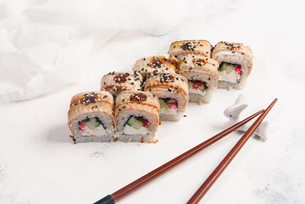 High angle view of sushi rolls with chopsticks and textile served on tableの写真素材 [FYI03750442]
