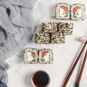 Overhead view of sushi rolls with dip and chopsticks by textile served on tableの写真素材 [FYI03750451]