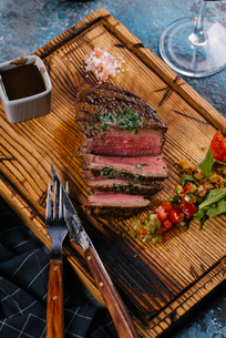 High angle view of grilled steak with dip and salad served on wooden boardの写真素材 [FYI03750522]