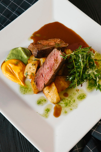 High angle view of beef steak served with vegetables and sauces in plate on tableの写真素材 [FYI03750570]