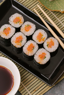 High angle view of sushi rolls served in tray with soy sauce and chopsticks on tableの写真素材 [FYI03750602]