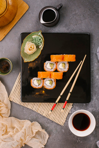 Overhead view of sushi rolls with decor served in plate with soy sauce and chopsticks on tableの写真素材 [FYI03750606]