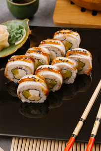 High angle view of sushi rolls served with chopsticks in tray on tableの写真素材 [FYI03750607]