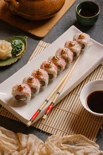 High angle view of sushi rolls with chopsticks served in tray on tableの写真素材 [FYI03750608]