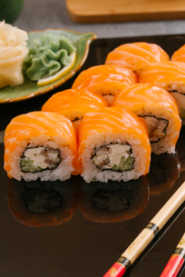 High angle view of salmon sushi rolls served with chopsticks in tray on tableの写真素材 [FYI03750609]