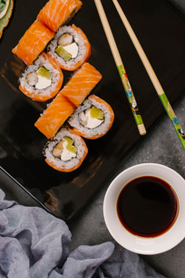High angle view of salmon sushi rolls served with chopsticks and soy sauce on tableの写真素材 [FYI03750611]