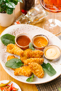 High angle view of chicken nuggets served with basil leaves and various sauces in white plate on tabの写真素材 [FYI03750663]