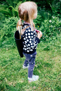 Side view of girl carrying arrows while standing on grassy field in forestの写真素材 [FYI03750810]