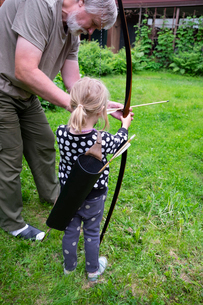 Grandfather teaching granddaughter archery while standing on grassy field at forestの写真素材 [FYI03750814]