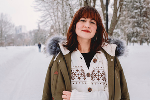 Portrait of woman with redhead standing on snow covered field in parkの写真素材 [FYI03750875]
