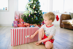 Cute boy with Christmas present sitting on hardwood floor at homeの写真素材 [FYI03751168]