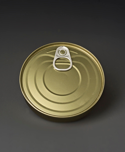 Close-up of closed golden tin can over gray backgroundの写真素材 [FYI03751271]