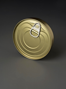 Close-up of golden tin can over gray backgroundの写真素材 [FYI03751277]