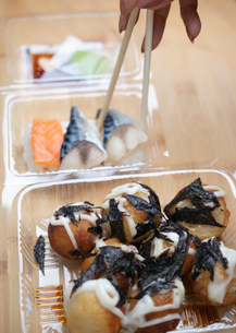 Cropped hand of woman picking sushi with chopsticks from plastic container on tableの写真素材 [FYI03751356]