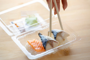 Cropped hand of woman picking seafood with chopsticks from plastic container on tableの写真素材 [FYI03751363]