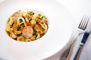 High angle view of sausage with pasta served in plate by cutleries on tableの写真素材 [FYI03751394]