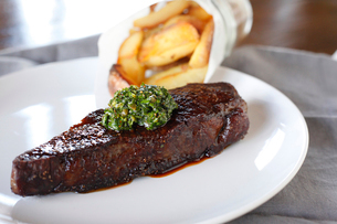 Close-up of steak with French fries served in plate on tableの写真素材 [FYI03751440]