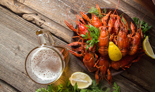 Overhead view of boiled crayfish served with beer on wooden tableの写真素材 [FYI03751693]