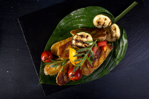 Overhead view of grilled halloumi cheese with cherry tomatoes, peppers and zucchini served in leaf oの写真素材 [FYI03751698]