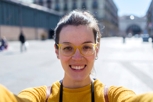 Portrait of smiling female tourist standing in city during sunny dayの写真素材 [FYI03752015]